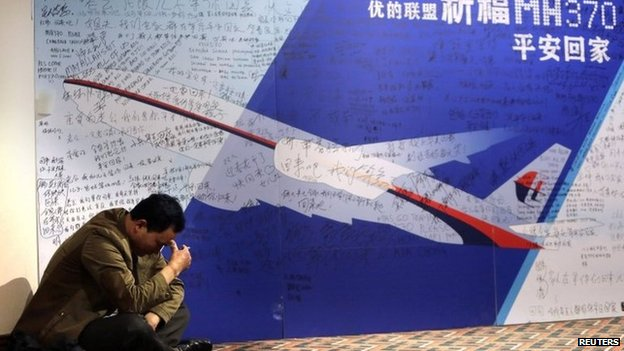 Relative of a Chinese passenger of Malaysia Airlines Flight MH370, smokes next to a message board dedicated to passengers, in Beijing, 29 March.