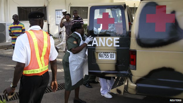 A military nurse helps victims of the blasts off an ambulance at the Asokoro General Hospital in Abuja (14 April 2014)