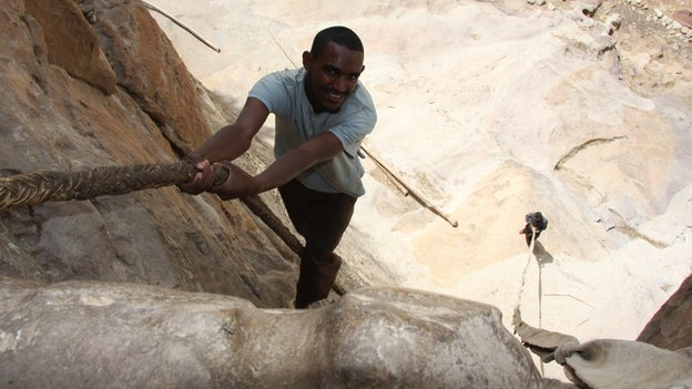 A young Ethiopian man ascends a 15m-high rock face with the aid of a leather rope to reach the cliff top monastery of Debre Damo, dating from the 6th century, in northern Ethiopia