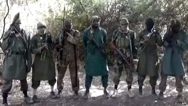 A picture taken from a video distributed to some Nigerian journalists and obtained by AFP on 5 March 2013 showing Boko Haram's leader Abubakar Shekau (C) flanked by six armed and hooded fighters in an undisclosed place