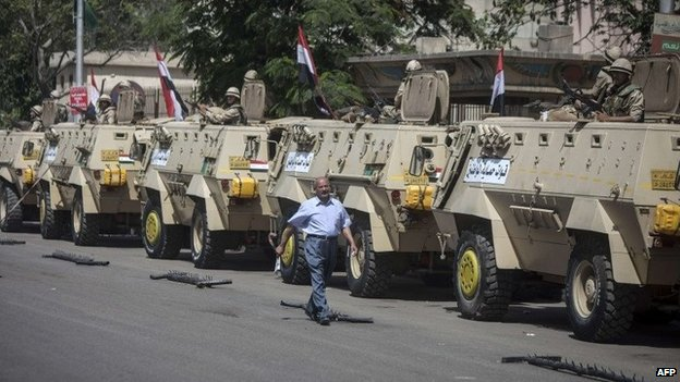 A man walks past armoured personnel carriers outside a polling station in Cairo (27 May 2014)