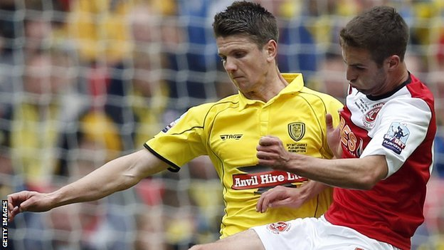 Shane Cansdell-Sherriff (left) tussles with Fleetwood Town's Matty Blair during the League Two play-of final