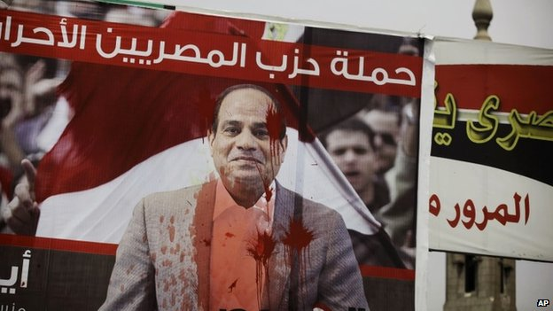 "A banner with the photo of presidential candidate Abdel-Fattah el-Sissi is splattered with red paint with Arabic that reads, ""free Egyptian party campaign,"" in Cairo, Egypt"