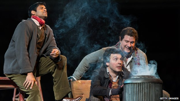 The artists and philosophers of Puccini's La Boheme burn a manuscript by Rudolfo, a poet, to stay warm