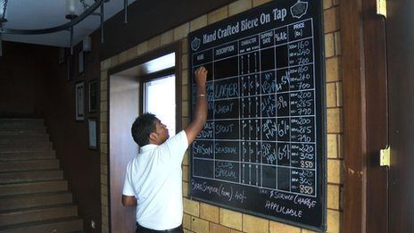 A board showing various craft beers in a pub