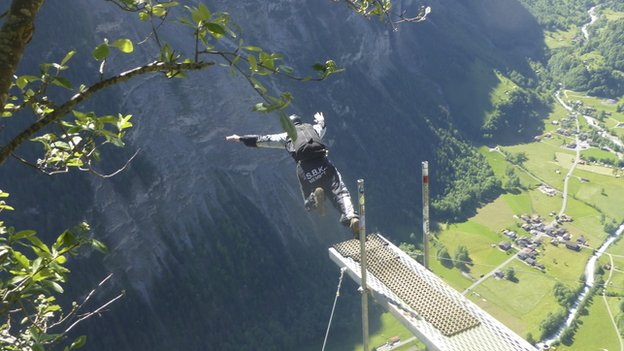 A base jumper jumps off a cliff