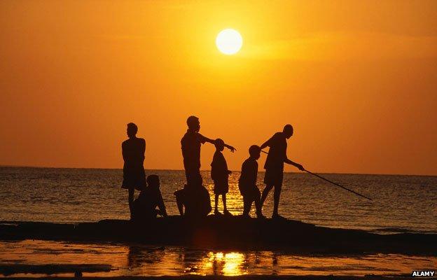 Aboriginal people fishing from rock outcrop, Galiwinku island, Arnhem Land