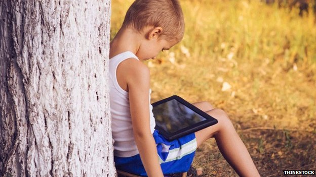 Boy using a tablet, lent against a tree