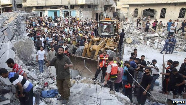 Palestinians search for anyone trapped in rubble in an overnight air strike in Rafah, 11 July