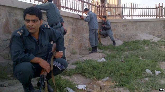 Afghan police take cover as fire is exchanged between insurgents and security forces at Kabul's airport early on July 17