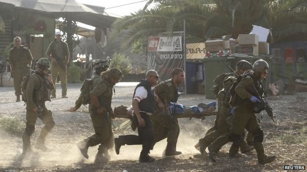 Israeli soldiers carry their comrade Gaza City and Israel's Eshkol hit by deadly bomb blasts