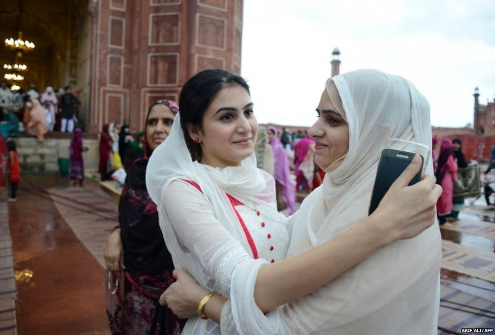 Pakistani Muslim devotees offer Eid greetings after prayers on the first day of the Eid al-Fitr festival at Badshahi Masjid in Lahore on July 29, 2014