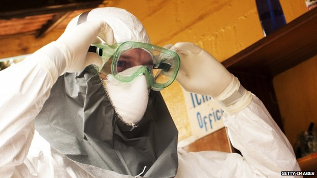 A person in a protective suit works at an Ebola isolation ward at a mission hospital outside of Monrovia, Liberia (4 August 2014)