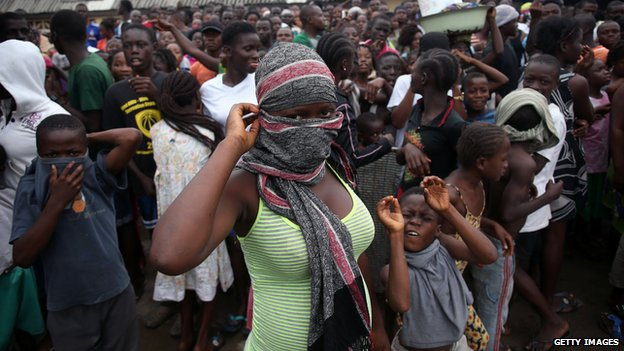 A crowd enters the grounds of an Ebola isolation center in the West Point slum on August 16 - https://ozaragossip.wordpress.com