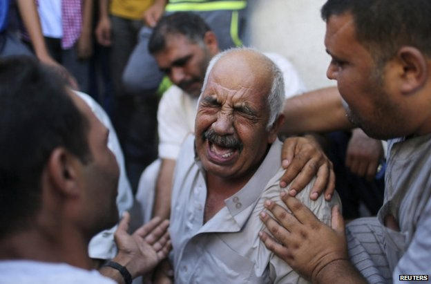 The grandfather of three children killed by an Israeli air strike weeps outside a morgue in Gaza City, 21 August
