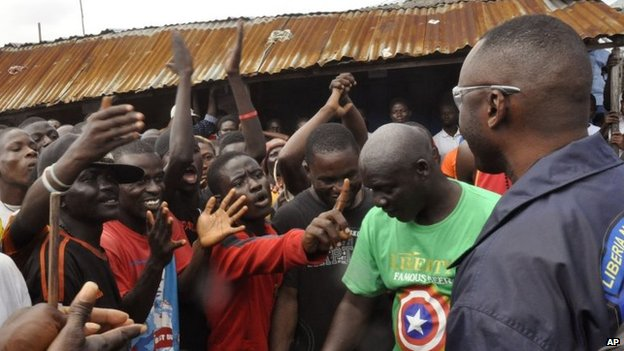 A Liberian policeman, right, speaks with residents of the West Point in Monrovia