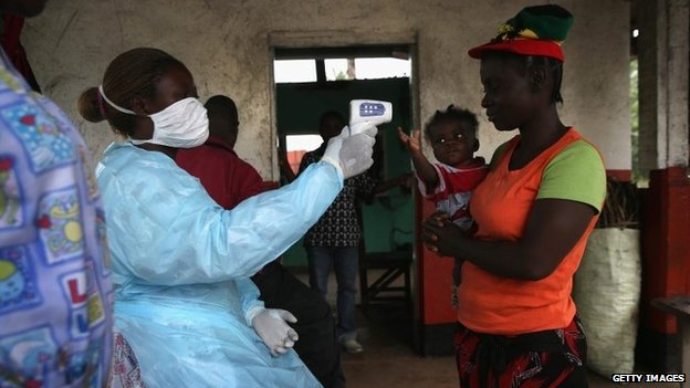 A Liberian Ministry of Health worker checks people for Ebola symptoms at a checkpoint near the international airport on August 24, 2014 near Dolo Town, Liberia.