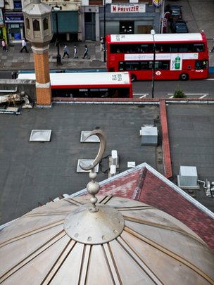 An aerial view of a mosque, with a road and two London buses in the background
