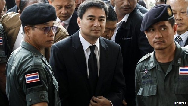 Democrat Party leader and former prime minister Abhisit Vejjajiva (centre) arrives at Bangkok criminal court in Bangkok, 12 December 2013