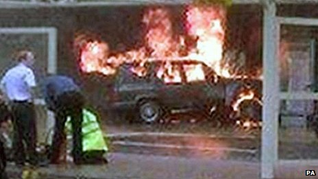 A burning jeep, with several people visible in the foreground (picture quality is low)