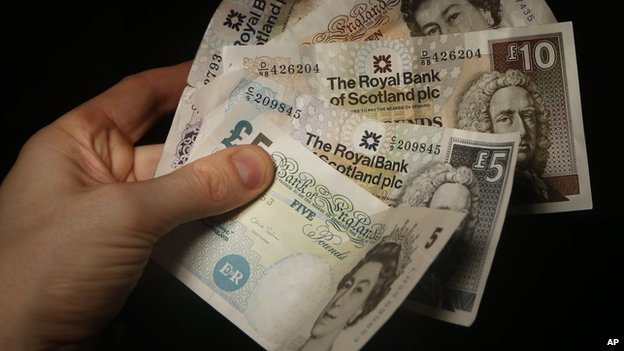 Somebody holding stirling pound notes and Scottish notes