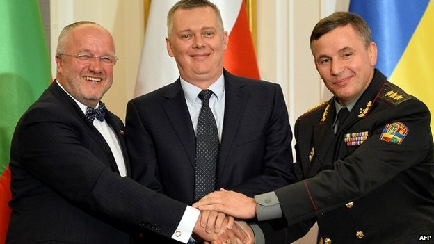 Ukrainian Defence Minister Valeriy Heletey (R), his Polish counterpart Tomasz Siemoniak (C) and Lithuanian counterpart Juozas Olekas (L) shake hands after signing an agreement on the creation of a joint military brigade - 19 September 2014