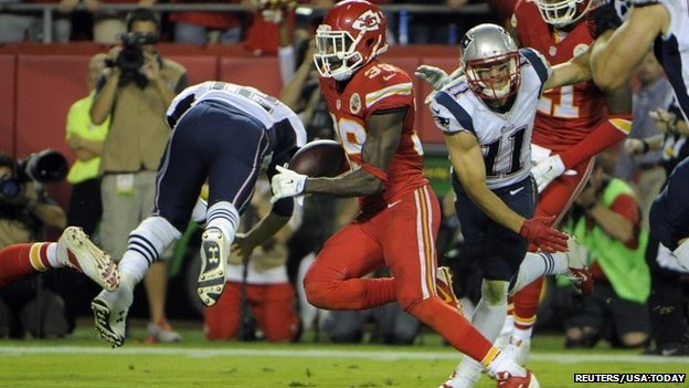 Husain Abdullah (Number 39) returns an interception for a touchdown against New England Patriots quarterback Tom Brady (Number 12) in the second half of the NFL football game in Kansas City.
