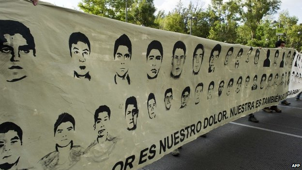 Protesters march with pictures of the missing students during a demonstration in Mexico City (8 October 2014)