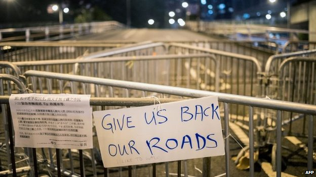 "A sign that says ""Give Us Back Our Roads"" is placed on a barricade on a highway in the Central district of Hong Kong, 10 October 2014"