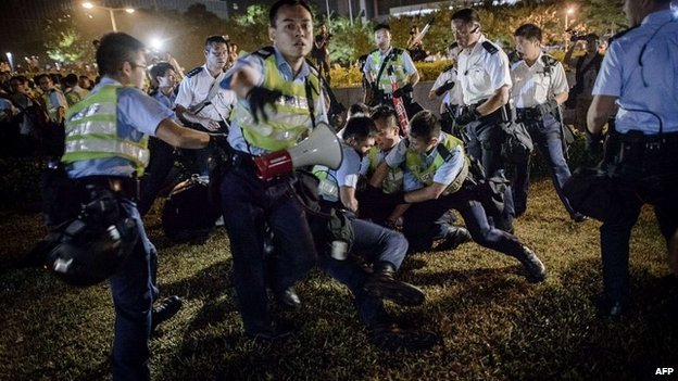 Police officers scuffle with pro-democracy protesters outside the central government offices in Hong Kong - 14 October 2014