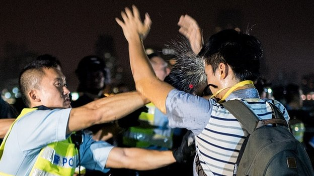 A police officer sprays a pro-democracy protester in the face with pepper spray in Hong Kong on October 15, 2014