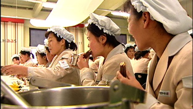 Still of North Koreans eating Choco Pie