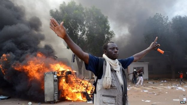 A man stands in front of a burning car, near the Burkina Faso's Parliament where demonstrators set fire to parked cars - 30 October 2014, Ouagadougou, Burkina Faso
