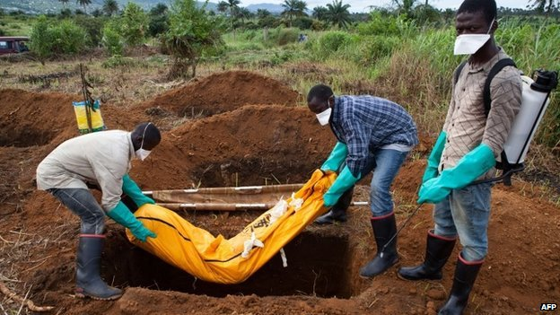 Volunteers in protective suits bury the body of a person who died from Ebola in a village outside Freetown, Sierra Leone - 7 October 2014