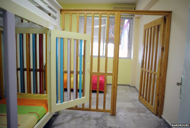 A caged bed and wooden bars separating a section of a room - some of the wood has been painted