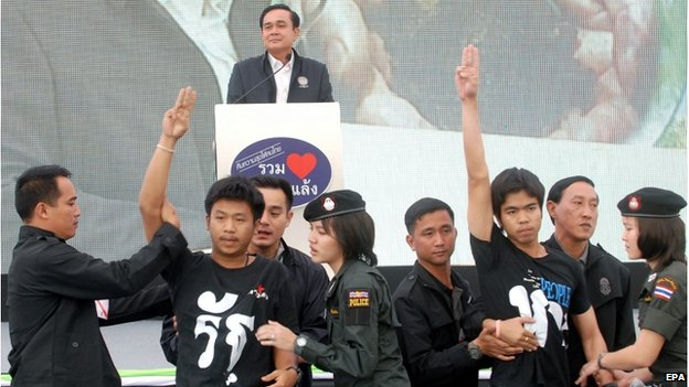 A photo made available on 20 November 2014 shows Thai students (front, 2-L and 3-R) being arrested by police officers and security guards as they flash anti-coup sign in front of Prime Minister Prayut Chan-ocha (back) while delivering a speech during his visit in Khon Kaen province, north eastern Thailand, 19 November 2014