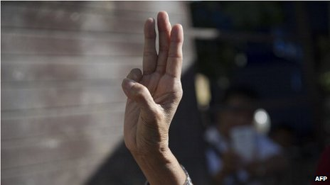 A woman flashes a three-finger salute during a gathering outside the Australian embassy on 4 June 2014 in Bangkok.
