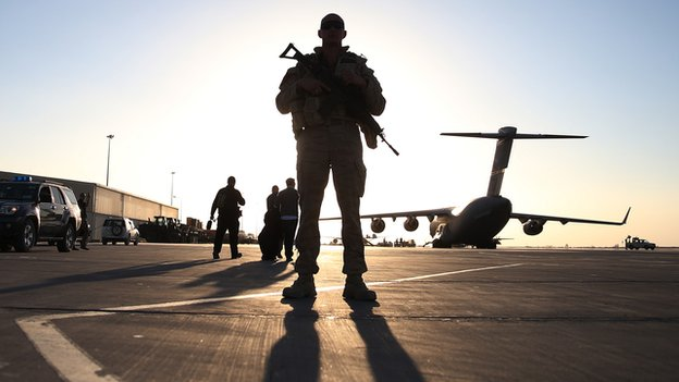 A soldier stands guard near a C17 military aircraft sitting on the tarmac, on 8 December 2013 in Kandahar.
