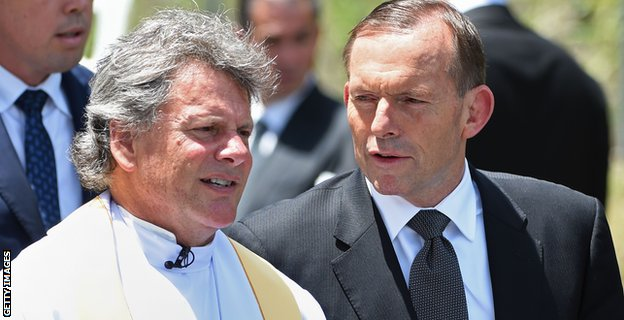Prime Minister Tony Abbott is greeted by Father Michael Alcock