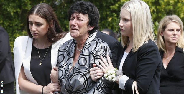 The mother of Hughes, Virginia, is comforted as she leaves the service