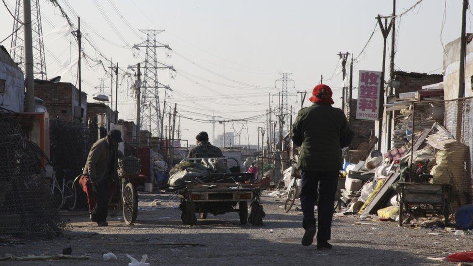 A group of men transport scrap materials along a road  in Dong Xiao Kou Village
