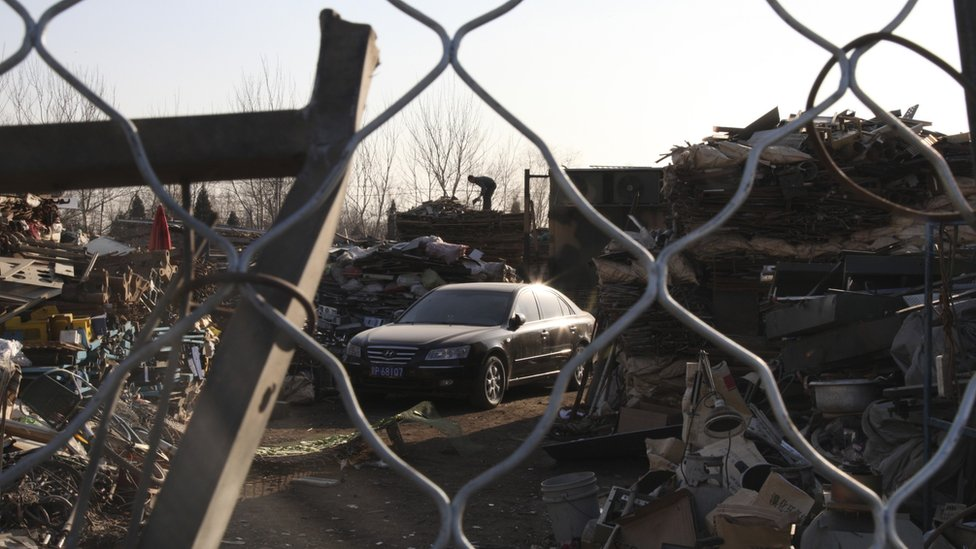 A flashy car is seen in the middle of a scrap yard in Dong Xiao Kou Village