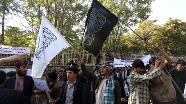 Afghan university students wave a black flag used by the Islamic State group and a white flag used by Taliban