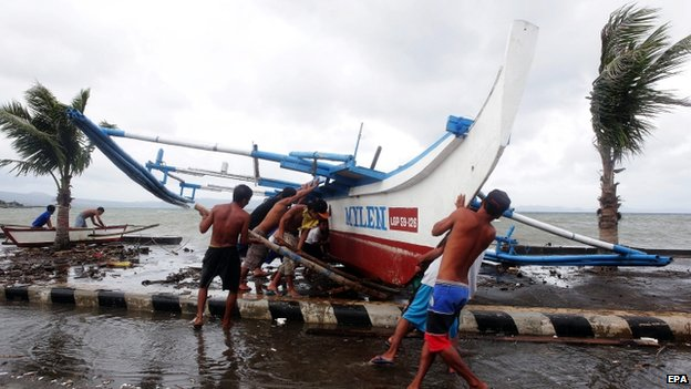 Filipino fishermen carry a fishing boat as strong winds brought by an upcoming typhoon hits Legazpi city, Albay province, Philippines, 5 December 2014