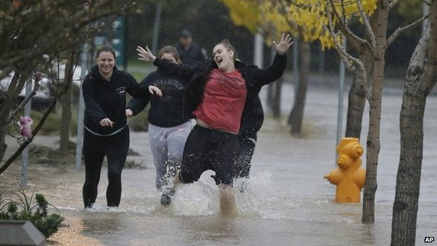 A group of girls laugh while running down a flooded street in Healdsburg, California 11 december 2014