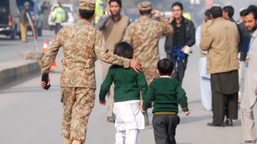 A soldier escorts schoolchildren away from a school attacked by gunmen in Peshawar