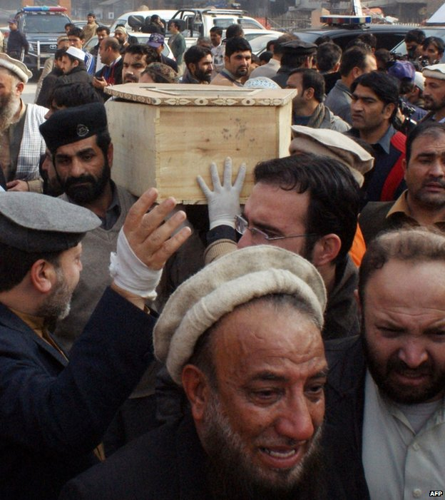 Mourners carry the coffin of a student from a hospital in Peshawar, 16 December