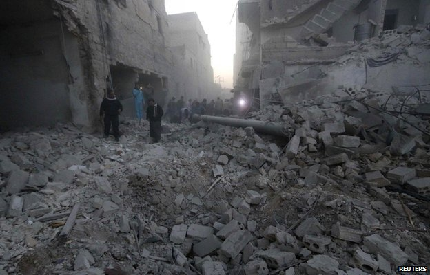 People inspect a site hit by what activists said was a barrel bomb dropped by forces loyal to Syria's President Bashar al-Assad on al-Marjeh neighbourhood of Aleppo November 12, 2014