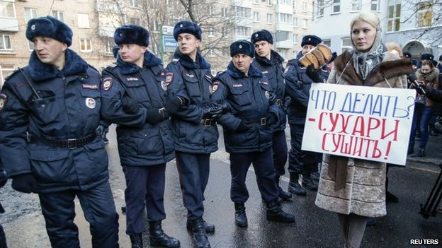 A supporter of opposition leader and anti-corruption blogger Alexei Navalny stands next to policemen blocking a street near a court building during his hearing in Moscow December 30, 2014