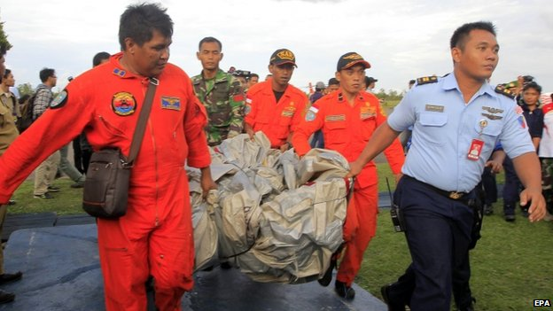 Indonesian air force crew carry what is believed to be slide from missing plane to military base in Pangkalan Bun - 30 December